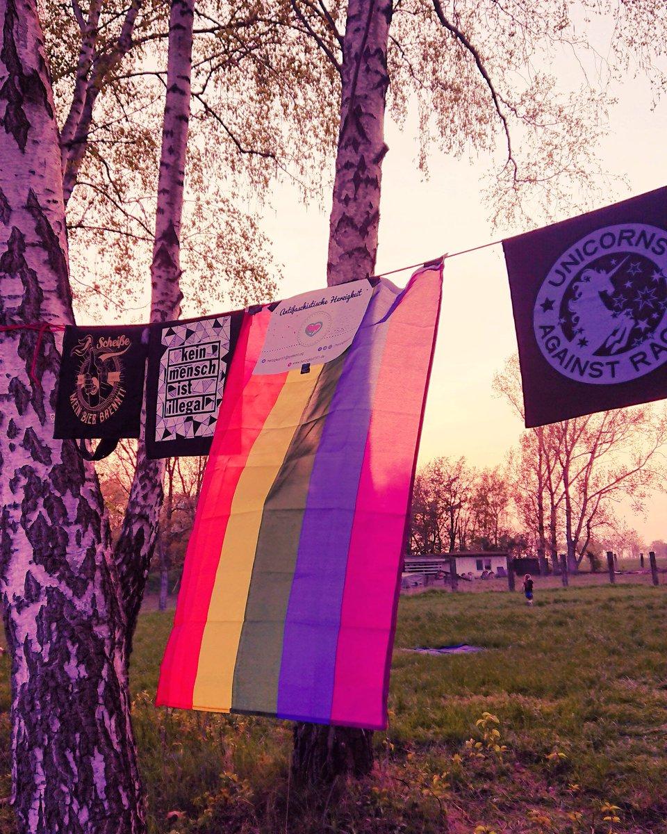Beutel der Antifaschistischen Herzigkeit und eine Regenbogenfahne hängen vor der untergehenden Sonne