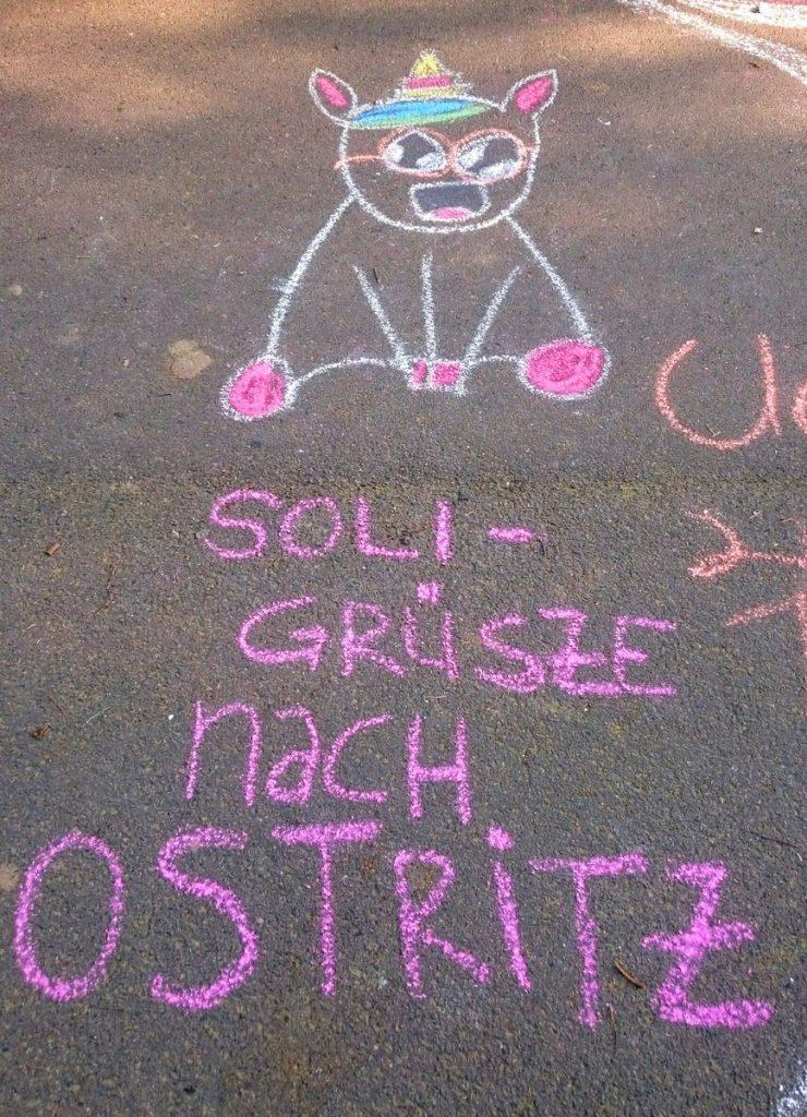 """""""Soligrüße nach Ostritz"""" steht mit Kreide geschrieben auf der Straße, darüber ein gemaltes Einhorn"""