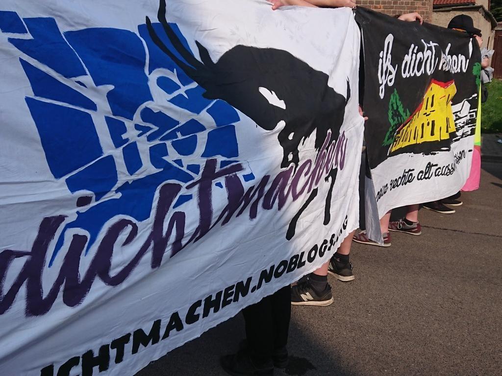 """Die Demonstration steht mit zwei Transparenten auf der Zwischenkundgebung vor dem """"Schäfchen"""""""